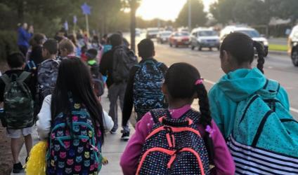 diverse young students walking to school