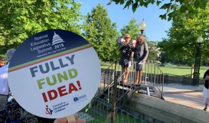 "Advocate at 2019 SELS rally holding up ""fully fund IDEA"" sign"
