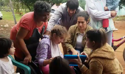Maria showing children in Paraguay assistive technology