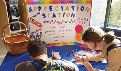 "A male and a female student sit writing notes in front of a bulletin board reading ""Appreciation Station"""