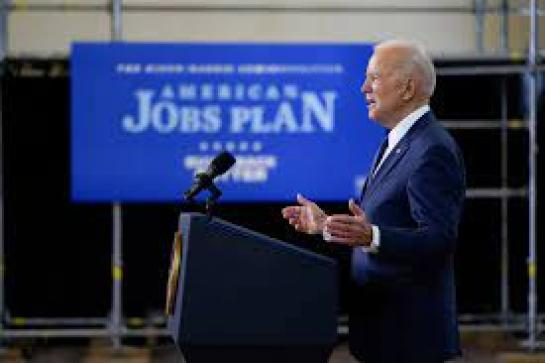 "President Biden speaking at a podium with a blue sign reading ""American Jobs Plan"" behind him"