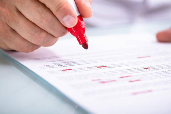 Close-up image of someone reading a document with a red marker in hand