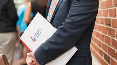 Man in suit holding a CEC document