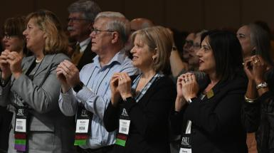board members standing with hands cupped at general conference session