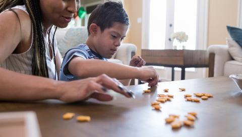 Woman working with young boy with disabilities sorting Goldfish crackers