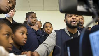 African American male educator surrounded by young African American students
