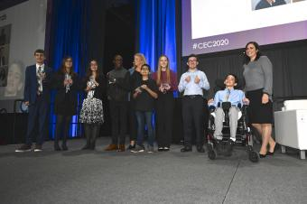 A group photo of the 2020 Yes I Can recipients smiling and posing on stage with their awards