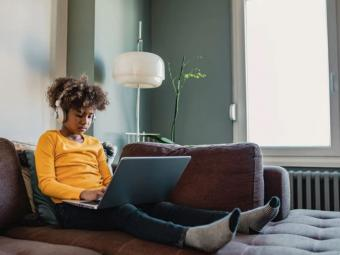 Young female African American student sitting on couch on her computer with headphones, focusing on schoolwork